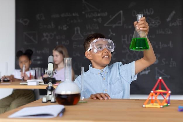 Młody chłopak uczy się więcej o chemii w klasie