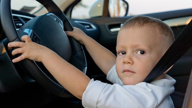 Młody chłopak udaje, że prowadzi samochód, siedzi za kierownicą i ma zapięty pas bezpieczeństwa