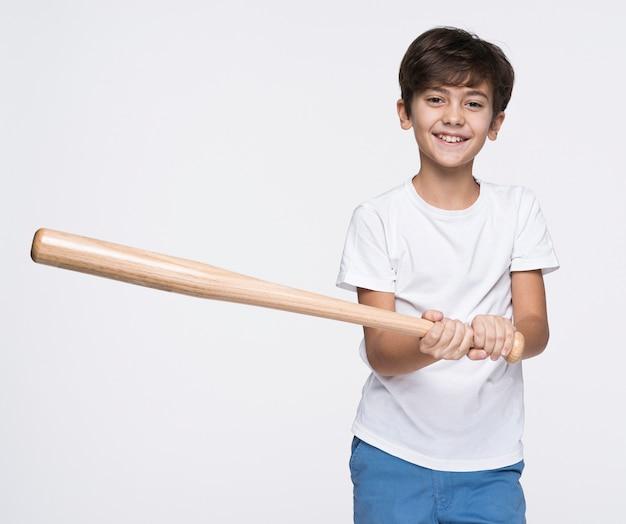 Młody chłopak uderza kijem baseballowym