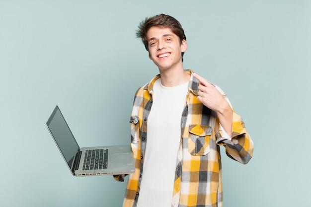 Młody chłopak uśmiechający się pewnie wskazując na swój szeroki uśmiech, pozytywną, zrelaksowaną, zadowoloną postawę. koncepcja laptopa