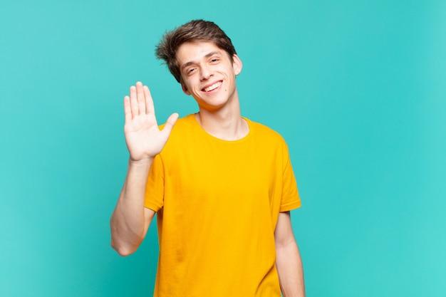 Młody chłopak uśmiechający się radośnie i radośnie, machający ręką, witający cię i pozdrawiający lub żegnający się