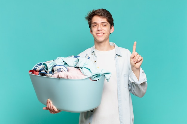 Młody chłopak uśmiechnięty i wyglądający przyjaźnie, pokazując numer jeden lub pierwszy z ręką do przodu, odliczając koncepcję prania ubrań