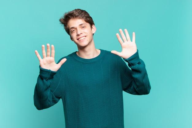 Młody chłopak uśmiechnięty i wyglądający przyjaźnie, pokazujący cyfrę dziesiątą lub dziesiątą ręką do przodu, odliczający w dół