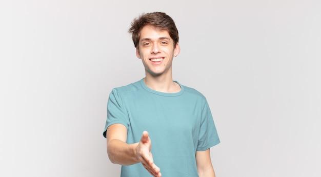 Młody chłopak uśmiechnięty, wyglądający na szczęśliwego, pewnego siebie i przyjacielskiego, oferujący uścisk dłoni w celu zawarcia umowy, współpracujący