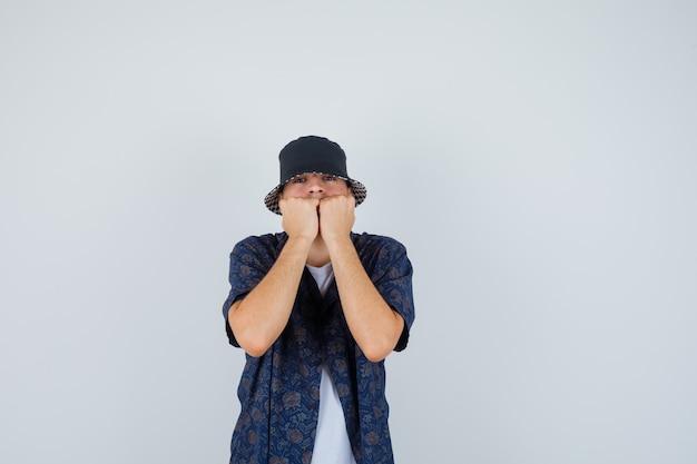 Młody chłopak w białej koszulce, kwiecistej koszuli, czapce, gryząc pięści i patrząc niespokojnie, widok z przodu.