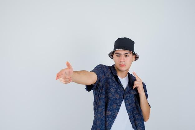 Młody chłopak w białej koszulce, kwiecistej koszuli, czapce pokazującej gesty pistoletu i wyglądającej na pewną siebie, widok z przodu.