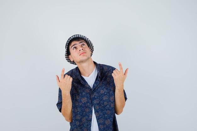 Młody chłopak w białej koszulce, kwiecistej koszuli, czapce skierowanej w górę palcami wskazującymi i patrząc skupiony, widok z przodu.