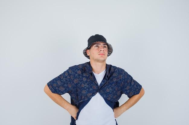 Młody chłopak w białej koszulce, kwiecistej koszuli, czapce, trzymając się za ręce w pasie i patrząc zamyślony, widok z przodu.