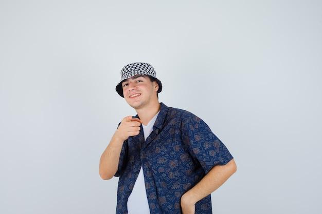 Młody chłopak w białej koszulce, kwiecistej koszuli, czapce, wskazując na aparat z palcem wskazującym i patrząc szczęśliwy, widok z przodu.