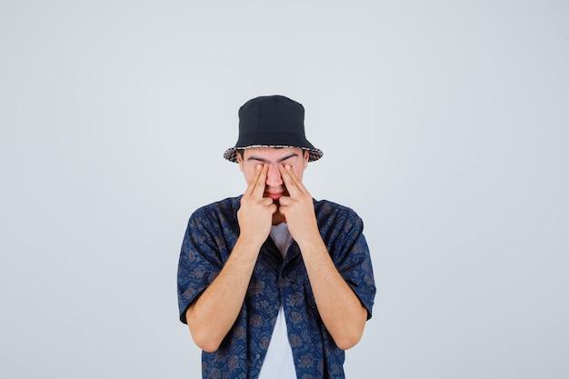 Młody chłopak w białej koszulce, kwiecistej koszuli, czapce zakrywającej oczy rękami i wyglądającej na zmęczoną, widok z przodu.