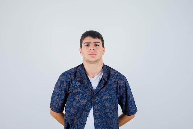 Młody chłopak w białej koszulce, kwiecistej koszuli, trzymając się za ręce w pasie i patrząc pewnie, z przodu.
