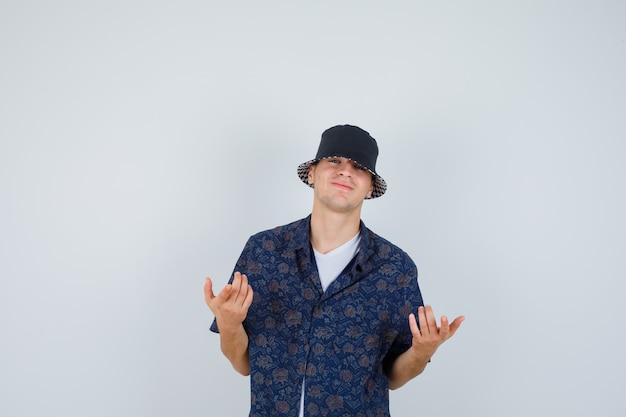 Młody chłopak w białej koszulce, kwiecistej koszuli, zachęcającej do przyjścia czapce i wyglądającej wesoło