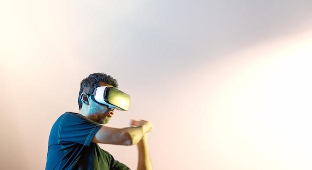Młody chłopak w czarnej koszulce z okularami wirtualnej rzeczywistości i uniesionymi rękami, jakby łapał kij baseballowy, patrząc w prawo, oświetlony żółtymi i niebieskimi światłami i kopiuj przestrzeń