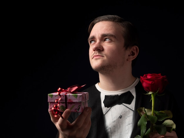 Młody chłopak w czarnym garniturze t-shirt trzyma czerwoną różę i różowy prezent w dłoniach patrząc na czarno