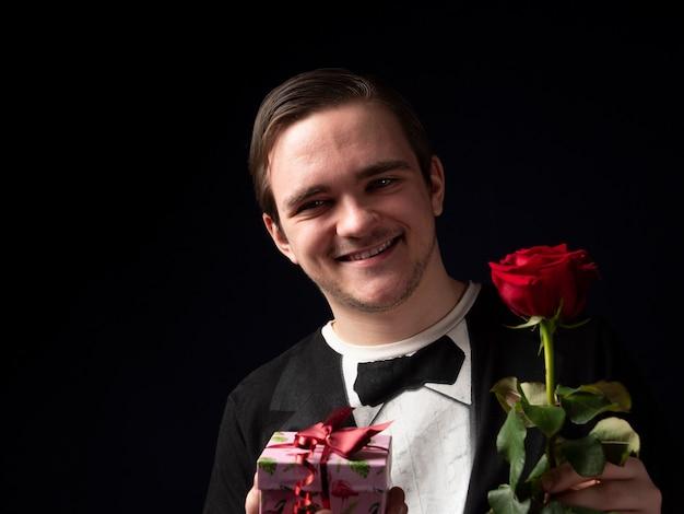 Młody chłopak w czarnym garniturze t-shirt trzyma czerwoną różę i różowy prezent w jego rękach uśmiechając się na czarno