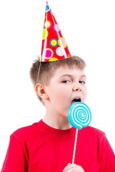 Młody chłopak w czerwonej koszulce i kapeluszu, jedzenie kolorowych cukierków - na białym tle