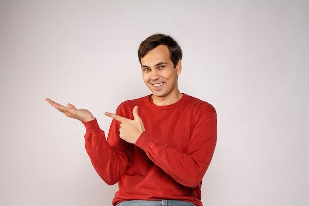 Młody chłopak w czerwonym swetrze śmieje się. portret