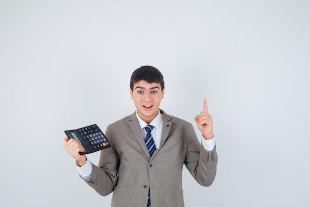 Młody chłopak w formalnym garniturze trzymając kalkulator, podnosząc palec wskazujący w geście eureki i wyglądający rozsądnie, widok z przodu.