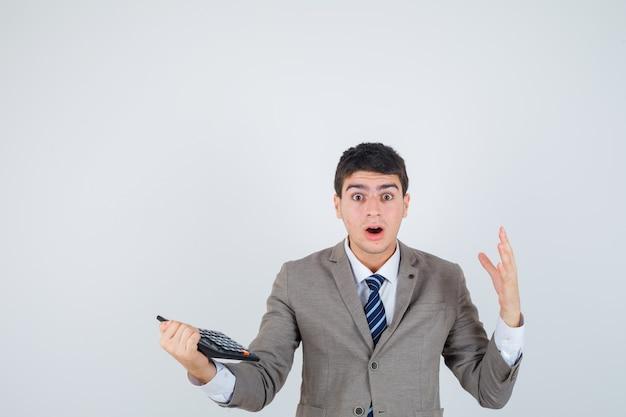 Młody chłopak w formalnym garniturze trzymając kalkulator, podnosząc rękę i patrząc zdziwiony, widok z przodu.