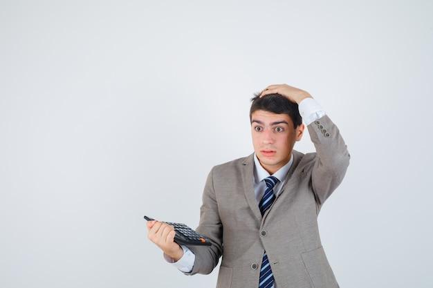 Młody chłopak w formalnym garniturze trzymając kalkulator, trzymając rękę na głowie i patrząc zamyślony, widok z przodu.