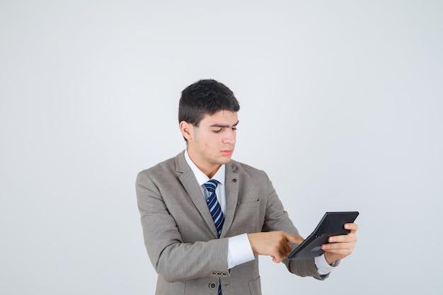 Młody chłopak w formalnym garniturze trzymając kalkulator, wykonując na nim pewne operacje i patrząc skoncentrowany, widok z przodu.