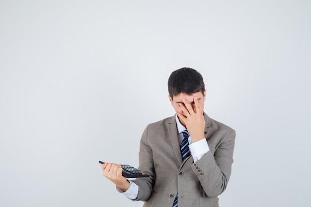Młody chłopak w formalnym garniturze trzymając kalkulator, zakrywający twarz ręką i wyglądający na zirytowanego, widok z przodu.