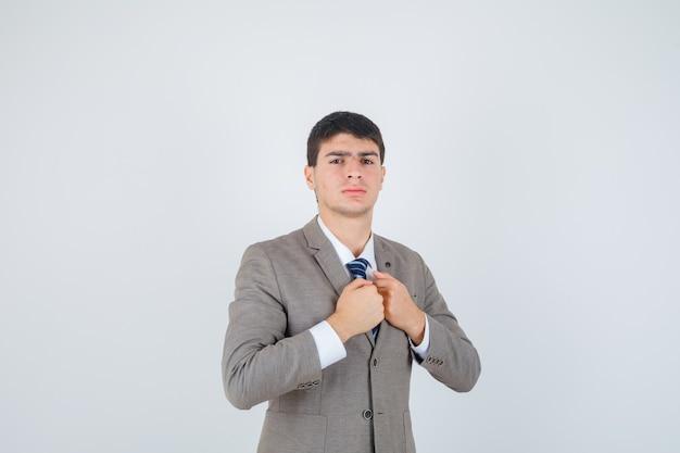 Młody chłopak w formalnym garniturze zaciskając pięści na klatce piersiowej i patrząc poważnie, z przodu.
