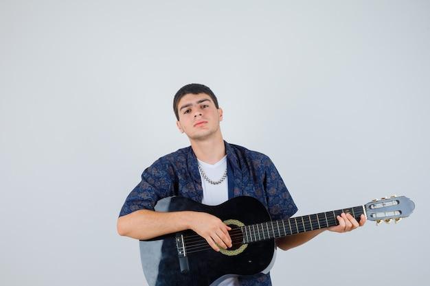 Młody chłopak w koszulce gra na gitarze siedząc aganista i patrząc pewnie, z przodu.