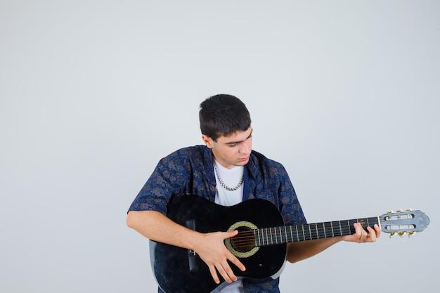 Młody chłopak w koszulce, grając na gitarze i patrząc pewnie, z przodu.
