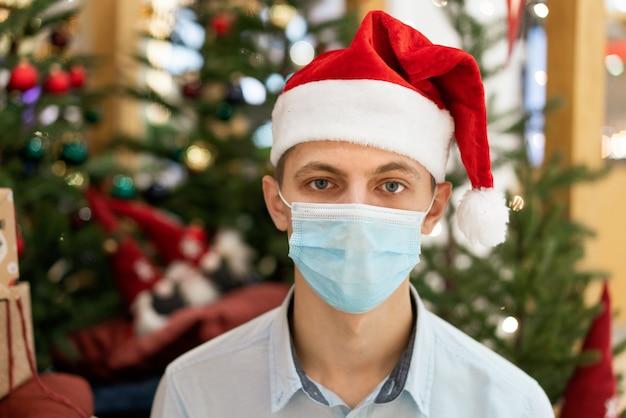 Młody chłopak w koszuli i czapce mikołaja na tle choinki. wakacje w czasie pandemii