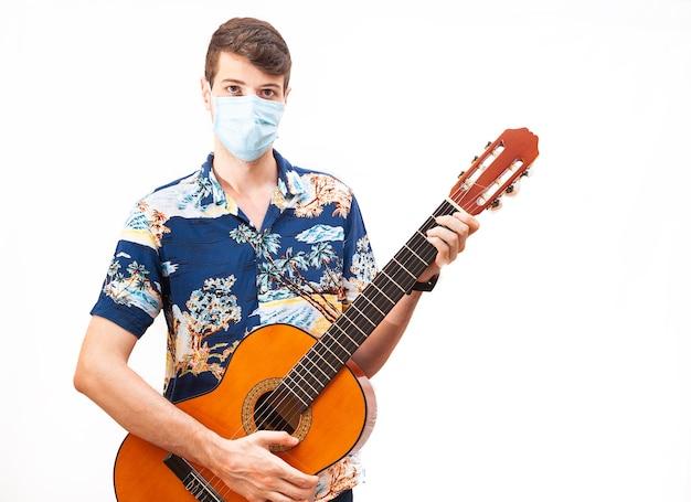 Młody chłopak w masce chirurgicznej, grający na hiszpańskiej gitarze