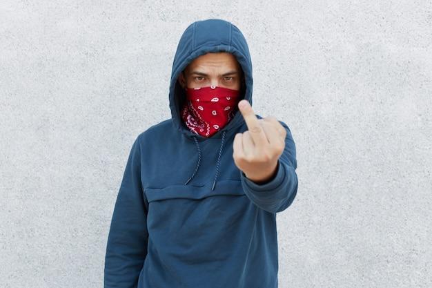 Młody chłopak w masce chustka wzywa do zatrzymania brutalności policji, pokazując środkowy palec