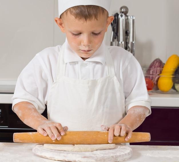 Młody chłopak w mundurze szefa kuchni toczenia ciasta