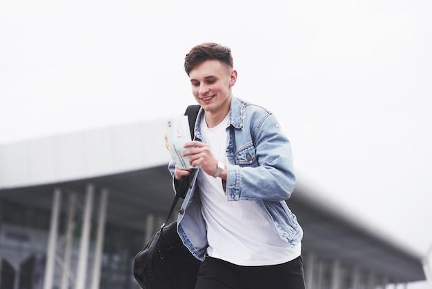 Młody chłopak w niebieskiej dżinsowej kurtce na ulicy.