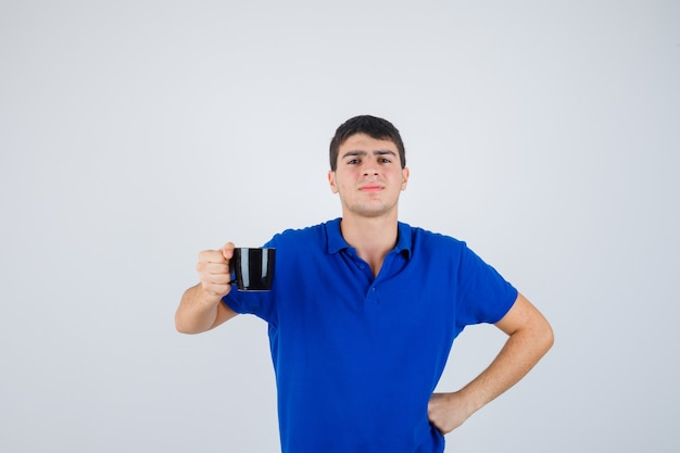 Młody chłopak w niebieskiej koszulce trzymając kubek, kładąc rękę na talii i patrząc pewnie, z przodu.