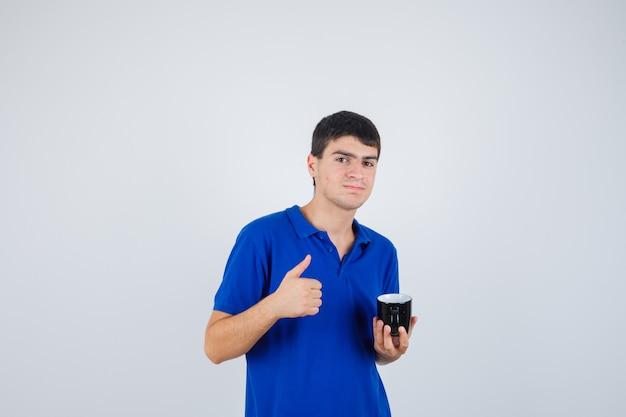Młody chłopak w niebieskiej koszulce trzymając kubek, pokazując kciuk do góry i patrząc szczęśliwy, widok z przodu.