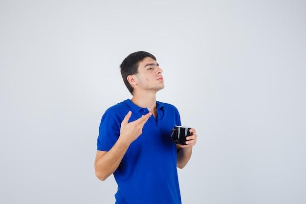 Młody chłopak w niebieskiej koszulce trzymając kubek, wyciągając rękę w pytający sposób i patrząc zamyślony, widok z przodu.