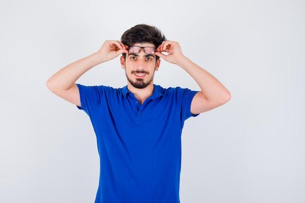 Młody chłopak w niebieskiej koszulce w okularach i patrząc szczęśliwy, widok z przodu.