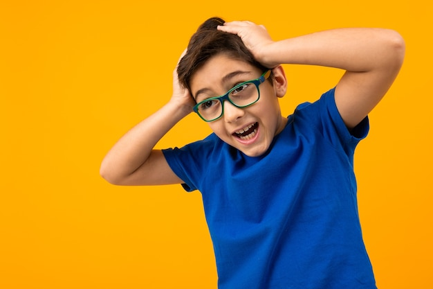 Młody chłopak w niebieskiej koszulce w okularach trzyma głowę