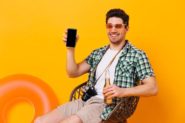 Młody chłopak w pomarańczowych okularach pokazuje swój telefon. pozytywny człowiek siedzi w drewnianym krześle, trzymając butelkę piwa i retro aparat.