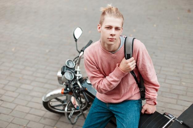 Młody chłopak w różowym swetrze i plecaku siedzi na motocyklu