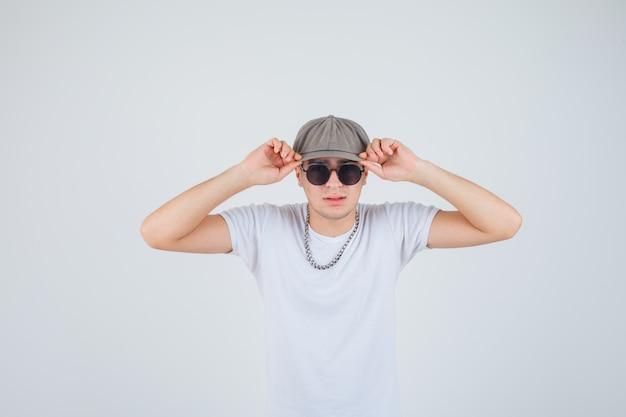 Młody chłopak w t-shirt, kapelusz, trzymając się za ręce na kapeluszu i wyglądający fajnie, widok z przodu.