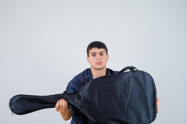 Młody chłopak w t-shirt, trzymając gitarę, patrząc na kamery i patrząc pewnie, widok z przodu.