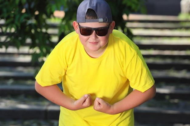 Młody chłopak w żółtej koszulce i ciemnych okularach pokazuje mięśnie. zdjęcie wysokiej jakości