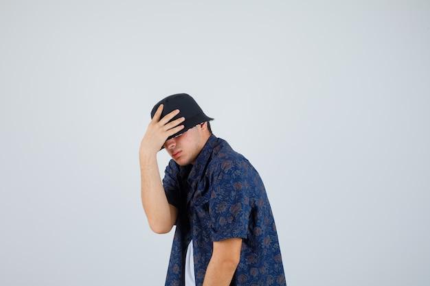 Młody chłopak wkłada ręce na czapkę w białej koszulce, kwiecistej koszuli, czapce i wygląda pewnie. przedni widok.