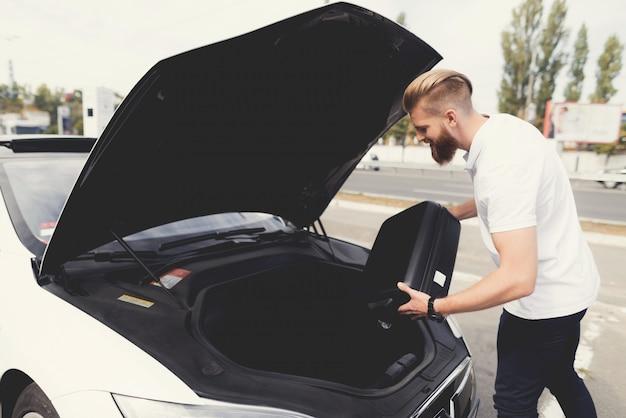 Młody chłopak włożył bagaż do bagażnika elektrycznego samochodu.