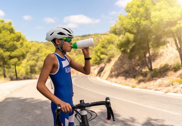Młody chłopak wody pitnej i energetyzujący napój i trzymając rower po jeździe na rowerze na zewnątrz na drodze
