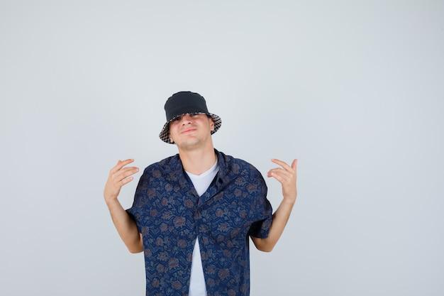 Młody chłopak, wskazując na siebie w białej koszulce, kwiecistej koszuli, czapce i patrząc pewnie na siebie, widok z przodu.