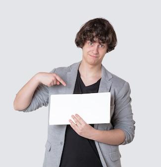 Młody chłopak wskazując palcem pusty znak
