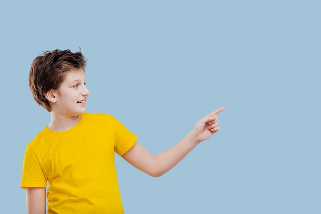 Młody chłopak wskazujący palcem na lewą stronę, w żółtej koszulce na niebieskim tle